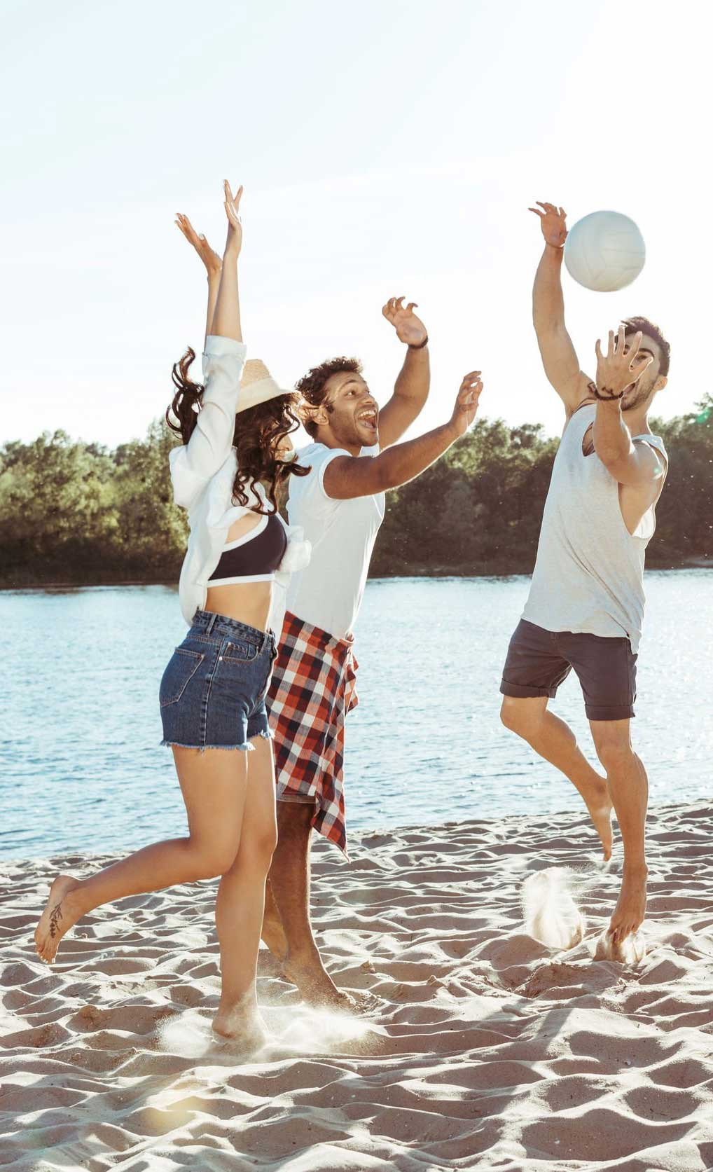 Friends playing volleyball on sandy